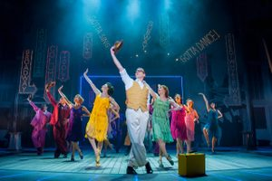 Company perform with bright coloured flapper dresses against a Broadway inspired backdrop